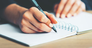 Person writing in a notepad