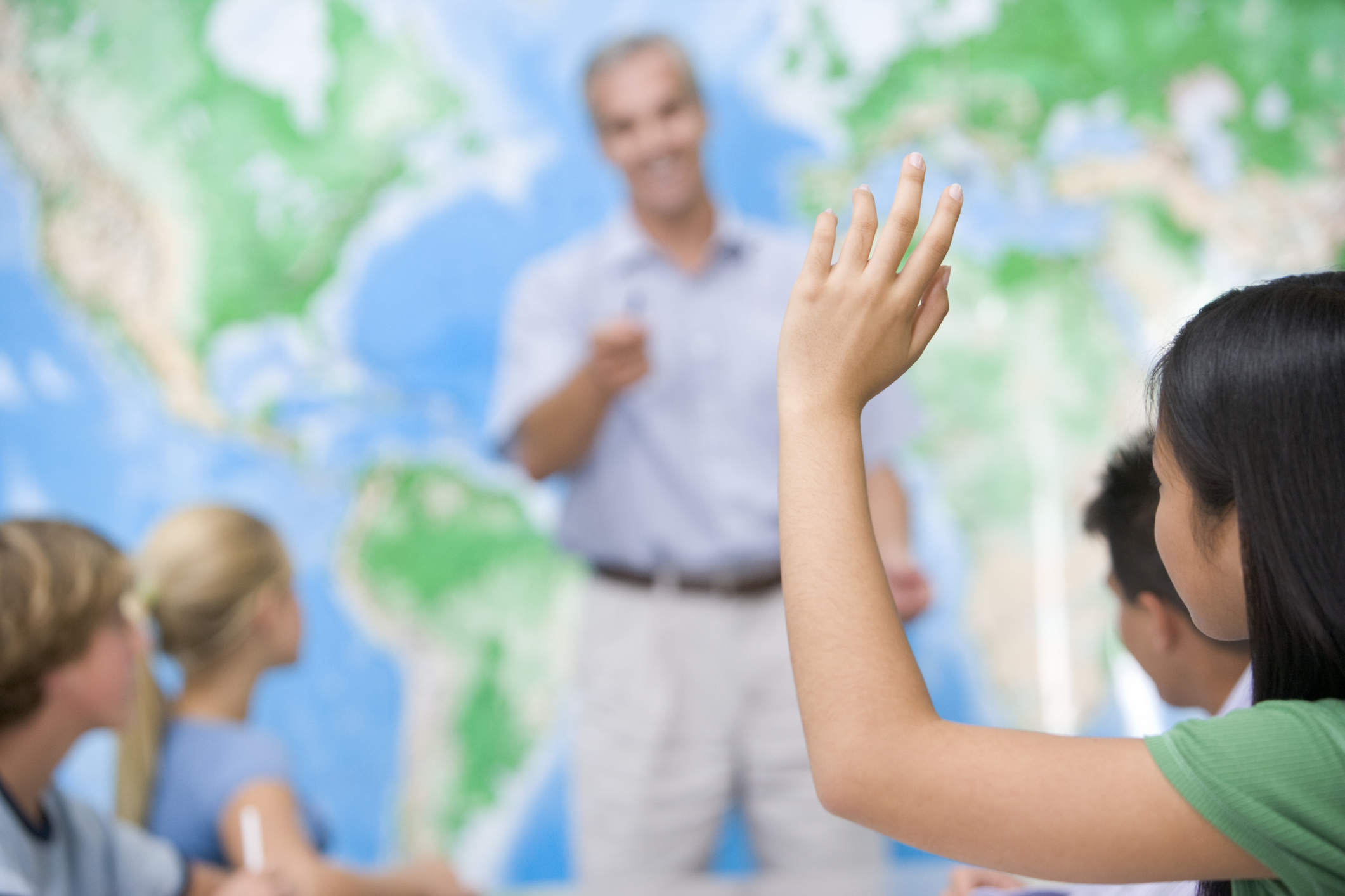Students ask questions in a geography class