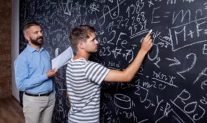 Teacher and student writing on big blackboard with mathematical calculations