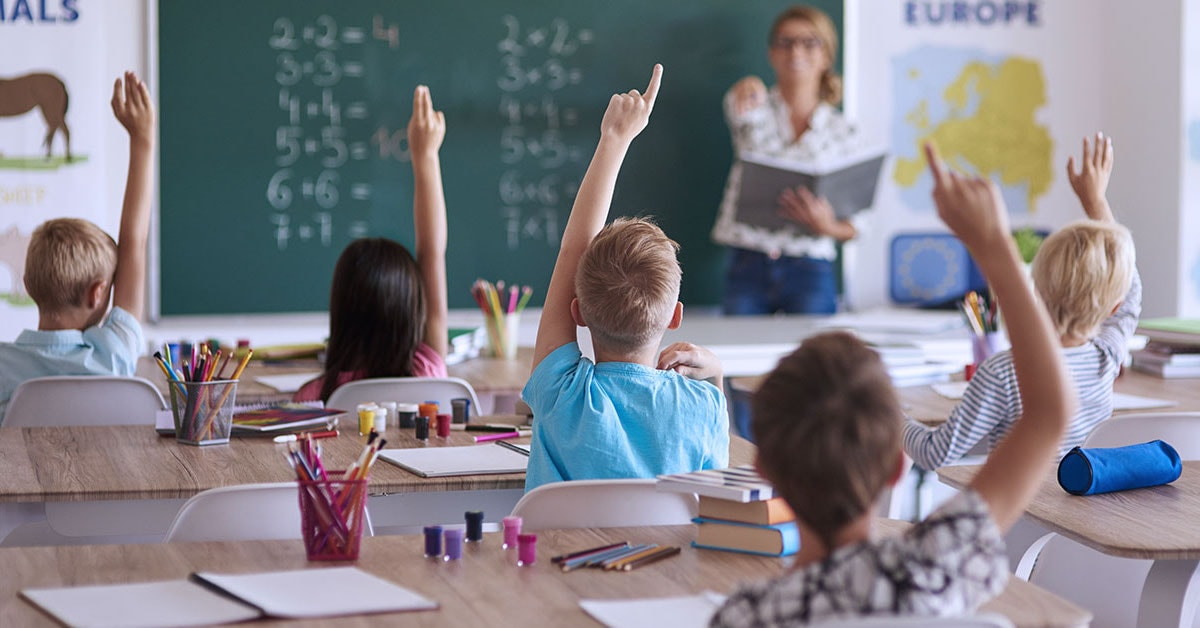 teacher with students hands raised