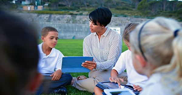 Teacher holding tablet teaching kids on grassfield
