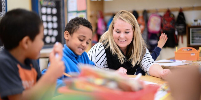 Female teacher helping young students