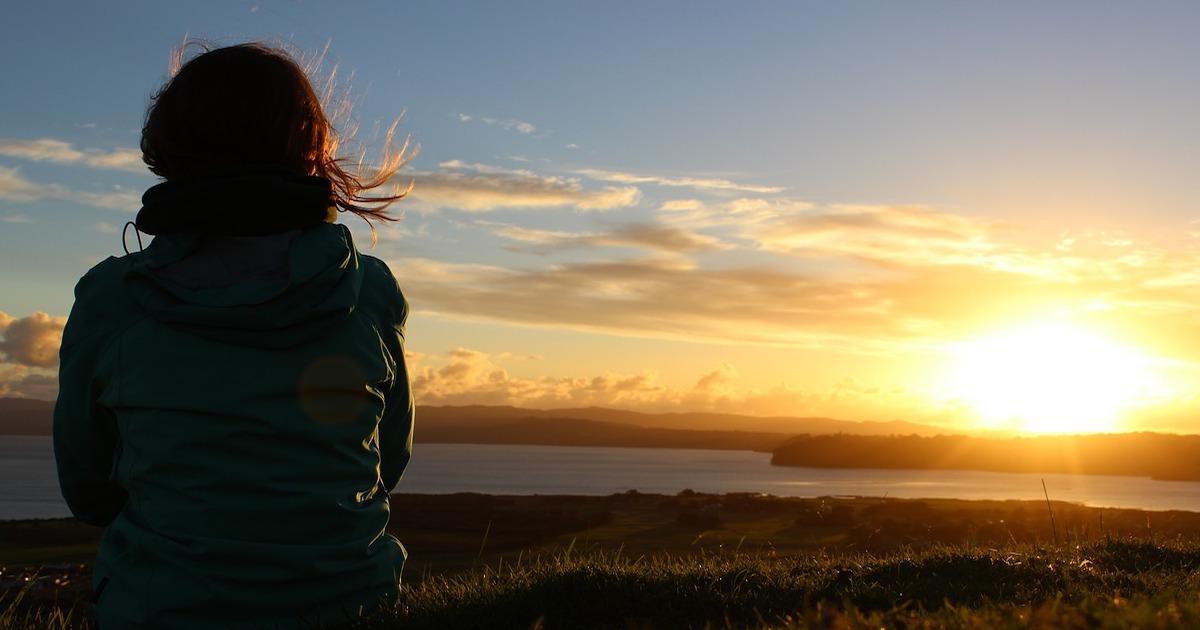 Woman staring at sunset.