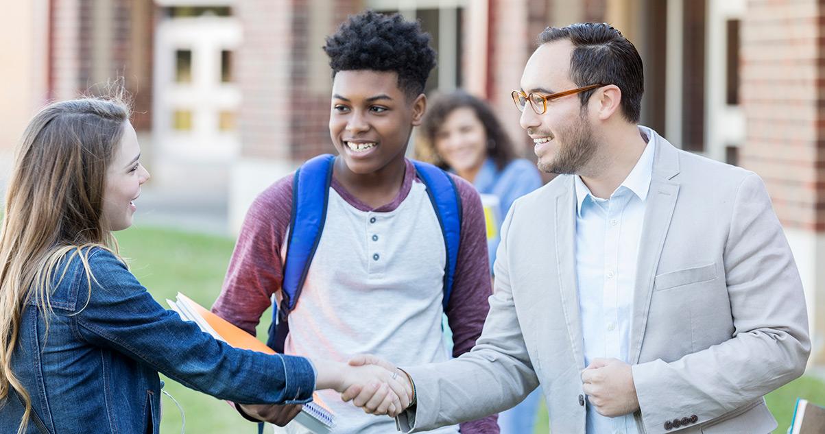 Teacher greeting nervous students before school starts