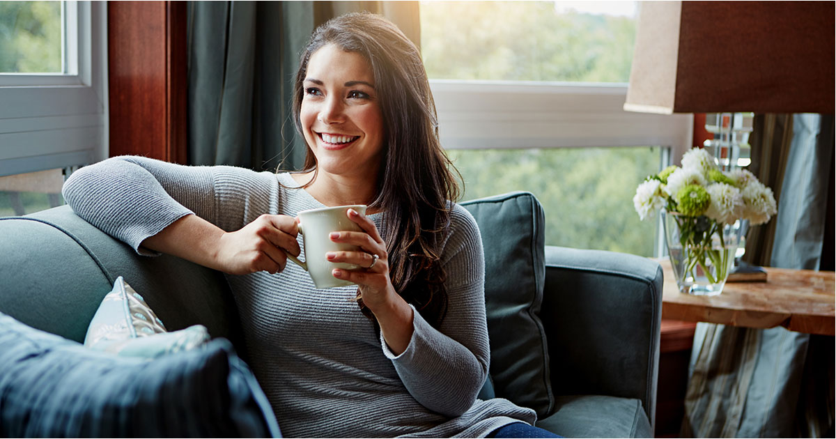 Teacher smiling while holding coffee cup.