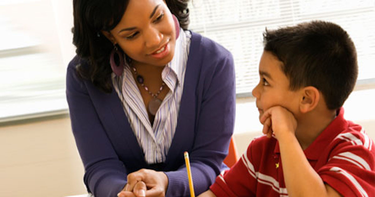 female teacher helping young male student