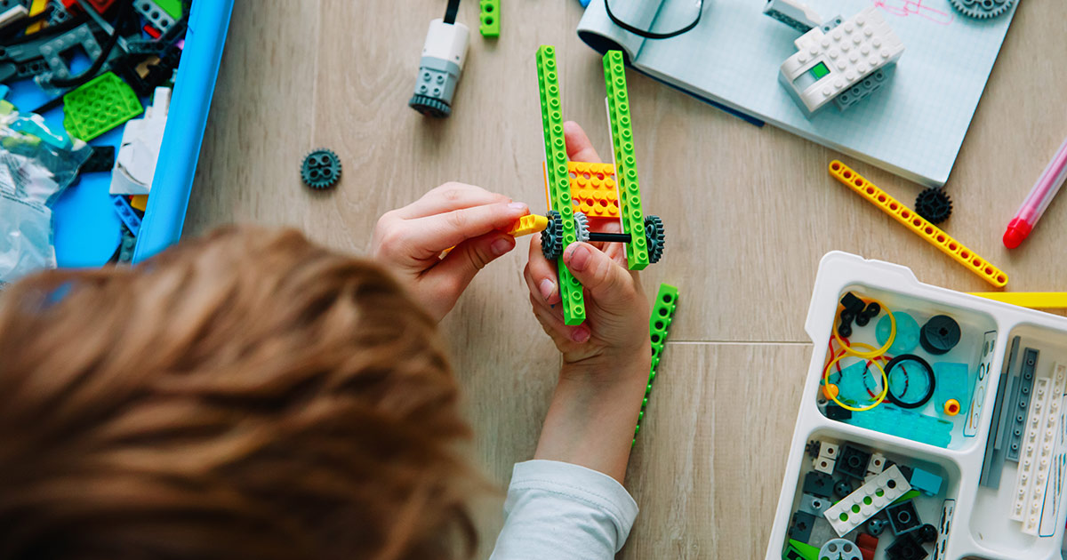 A child working with Legos in STEAM class