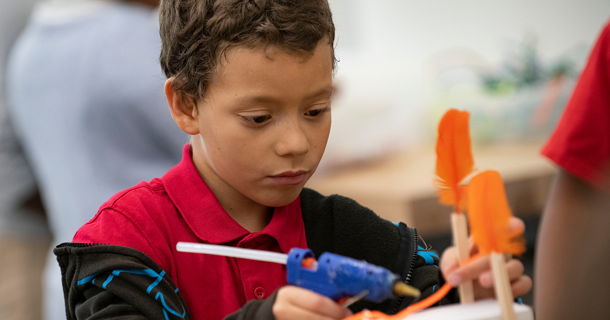A student working on a STEAM project with a hot glue gun