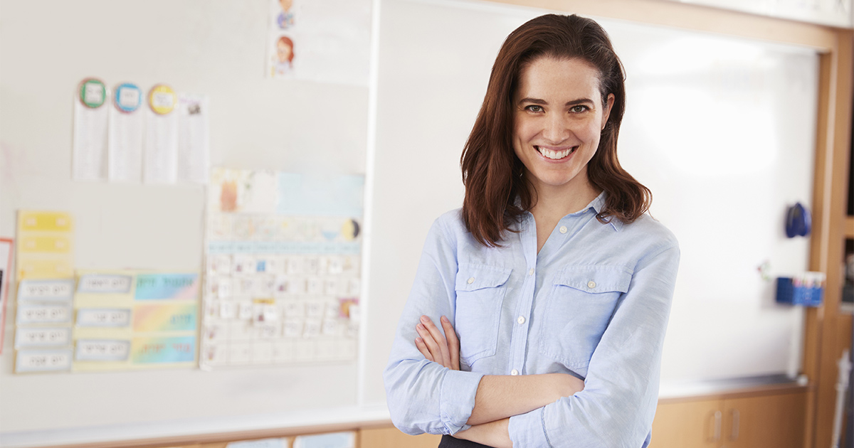 Lady standing in front of a corkboard.