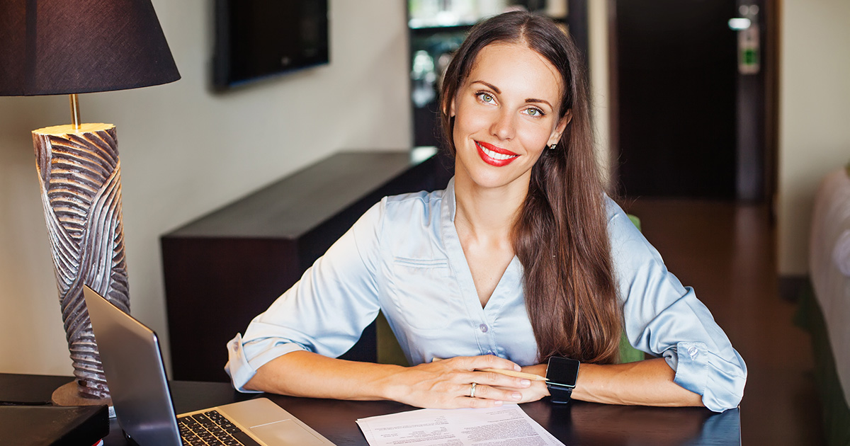 Lady sitting at desk and smiling.
