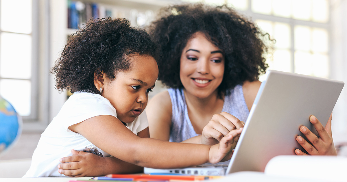 Woman helping child read on a laptop