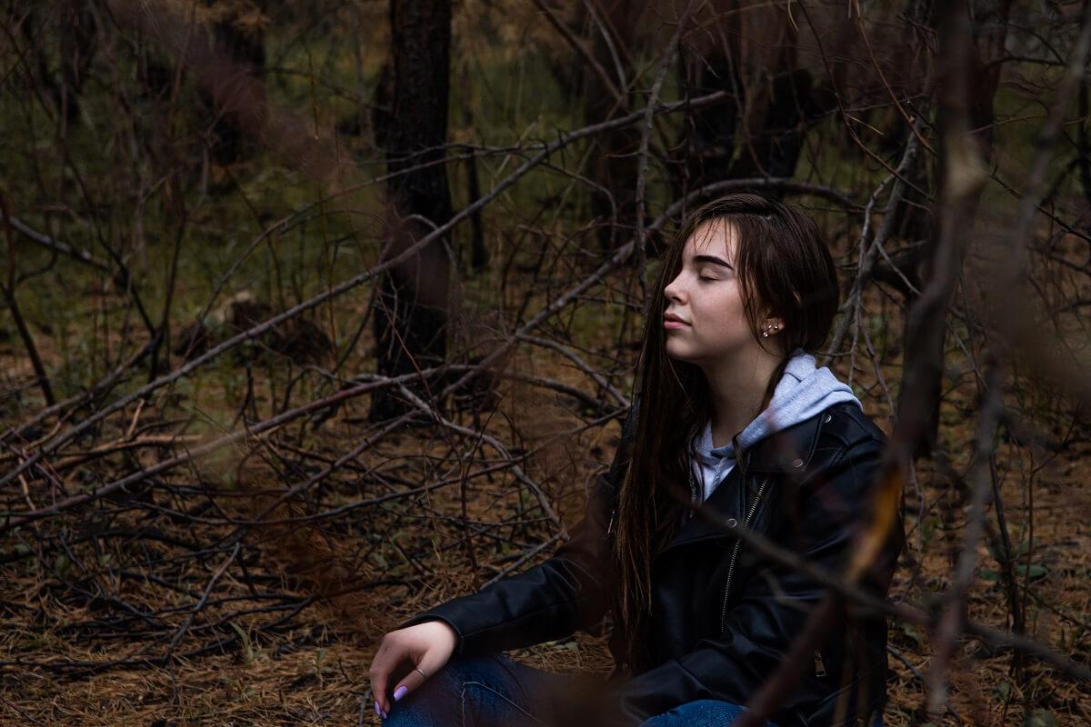 Woman meditating in rain inside the woods