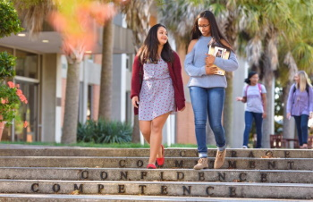 Two students walking down steps