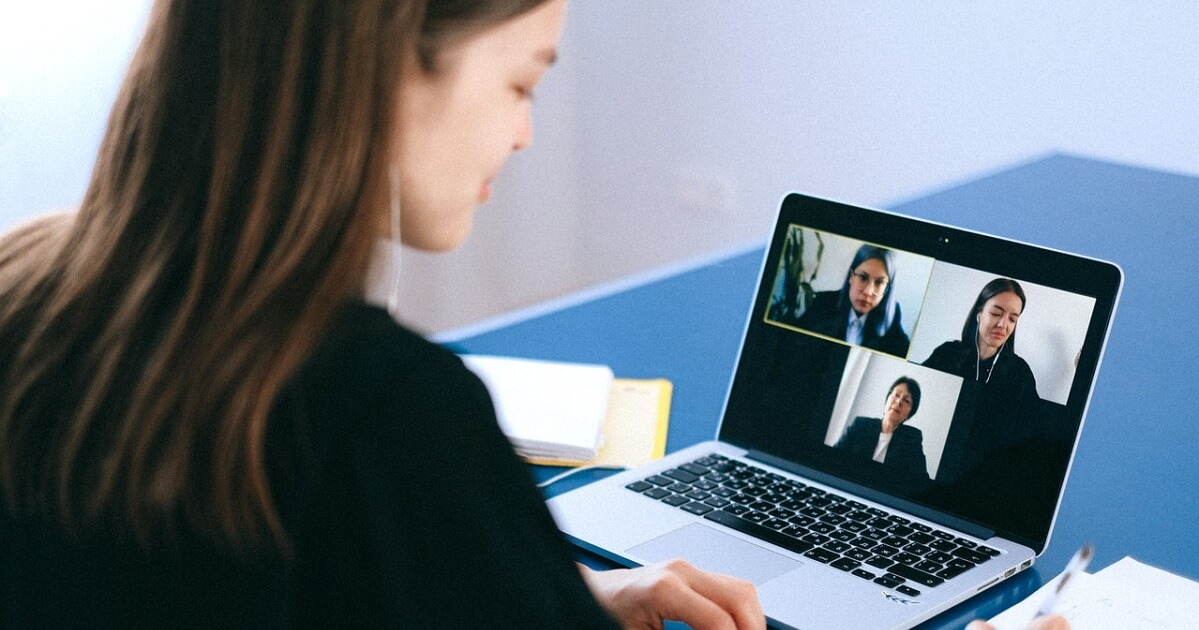 Lady taking notes during a videoconference