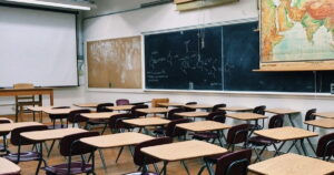 Empty classroom photo with world map hanging on the wall and chalkboard