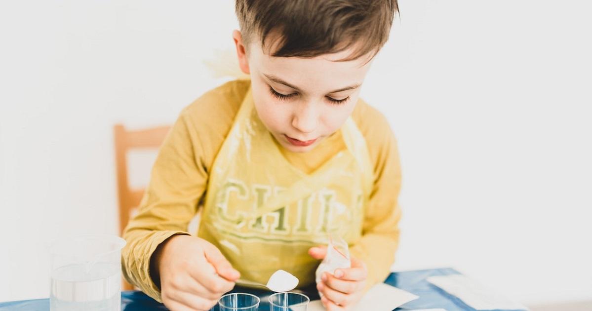 Kid using bottles on kitchen table doing science stuff