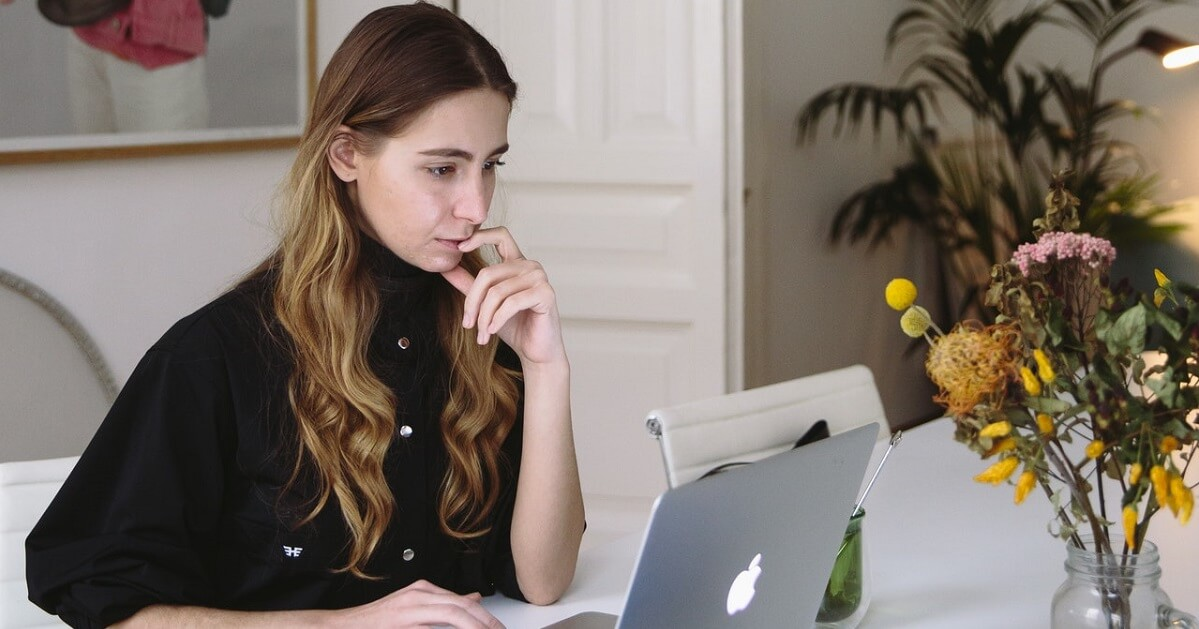Lady typing on laptop with fine art hanging behind her
