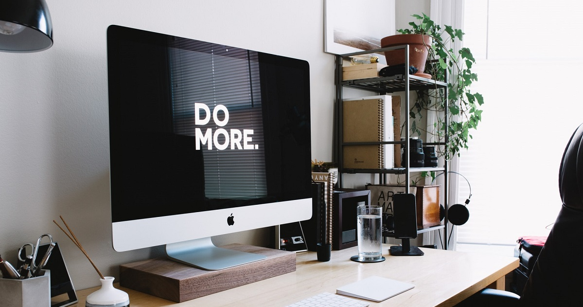 Laptop screen that says DO MORE on desktop in lighted office.