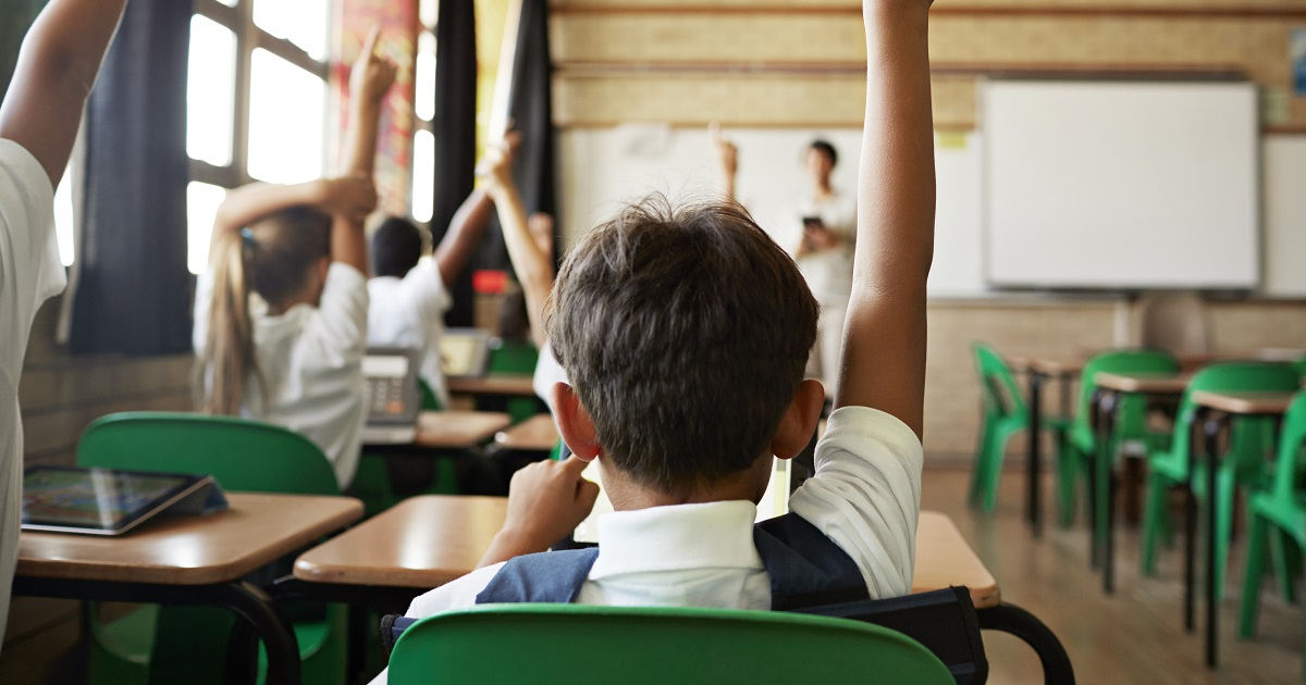 Student in classroom desk raising hand