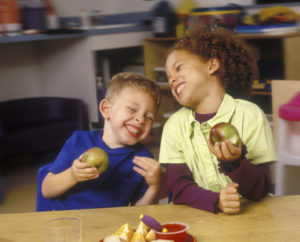 Elementary school children eat apples as part of a nutrition lesson.