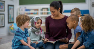 A teacher reading a book with ESL students