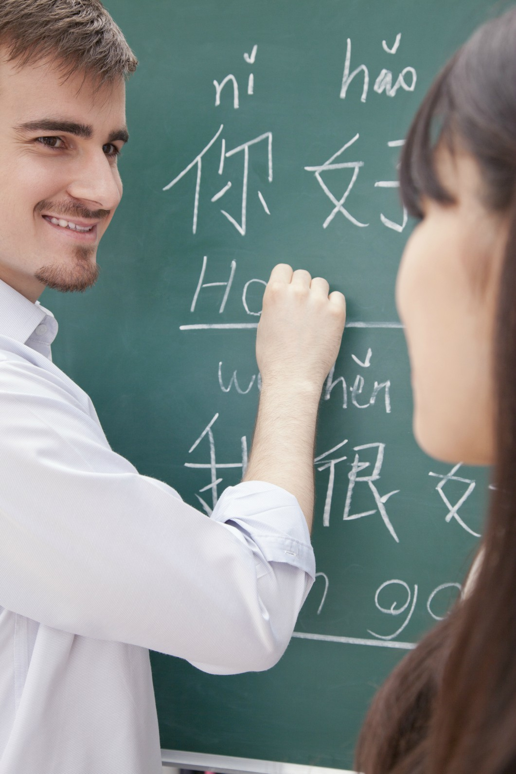College foreign language instructor works with student at blackboard