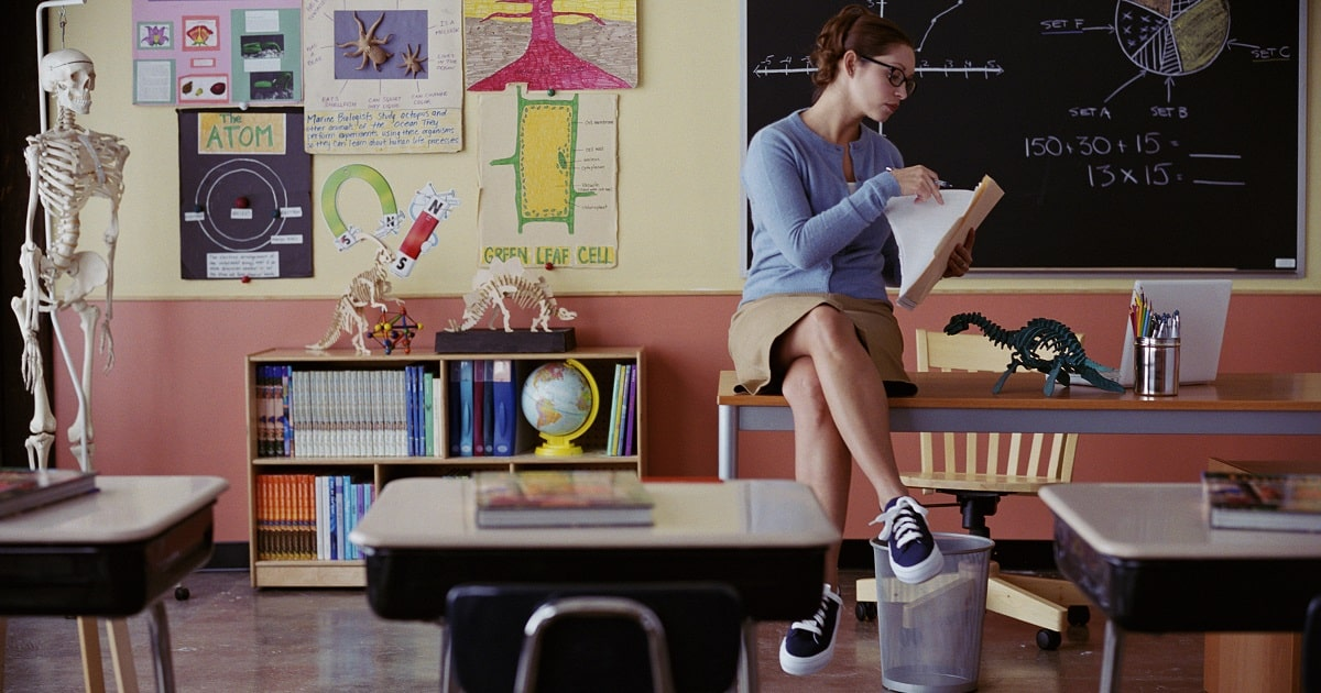 Teacher sitting on desk, reviewing collected papers in a folder inside the classroom.