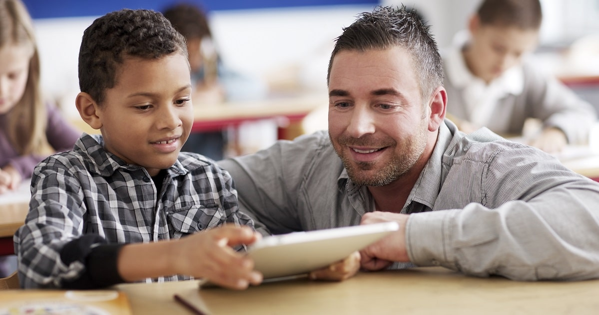 Teacher giving mentorship to student in a classroom.