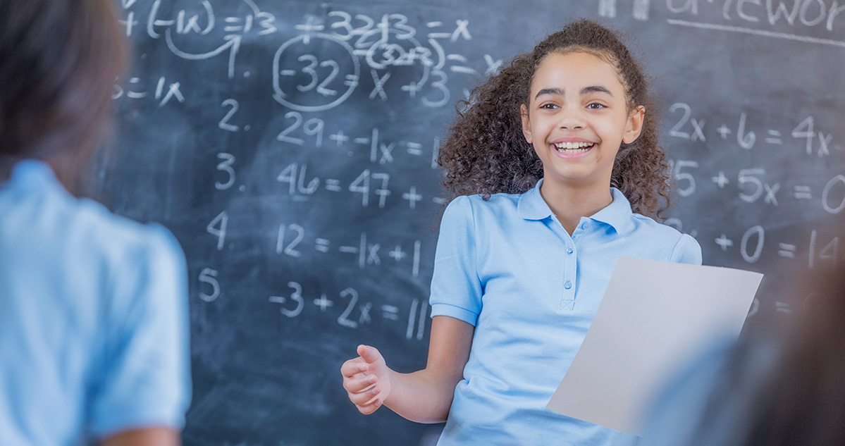 A middle school student doing math problems on a chalkboard
