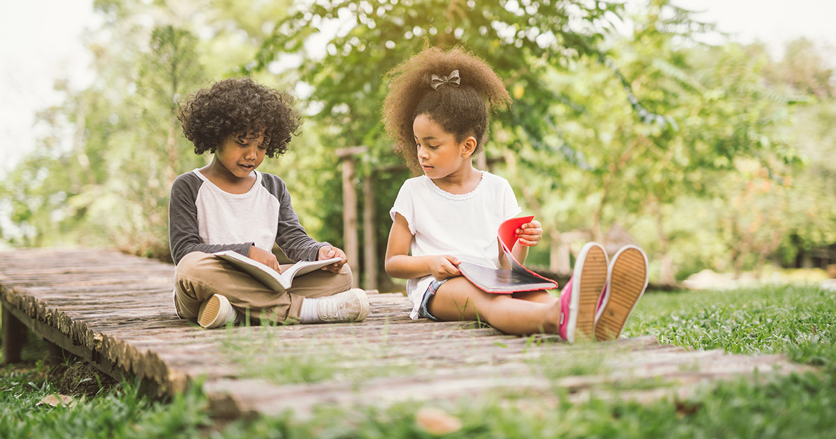 Kids reading books together on a beautiful summer day