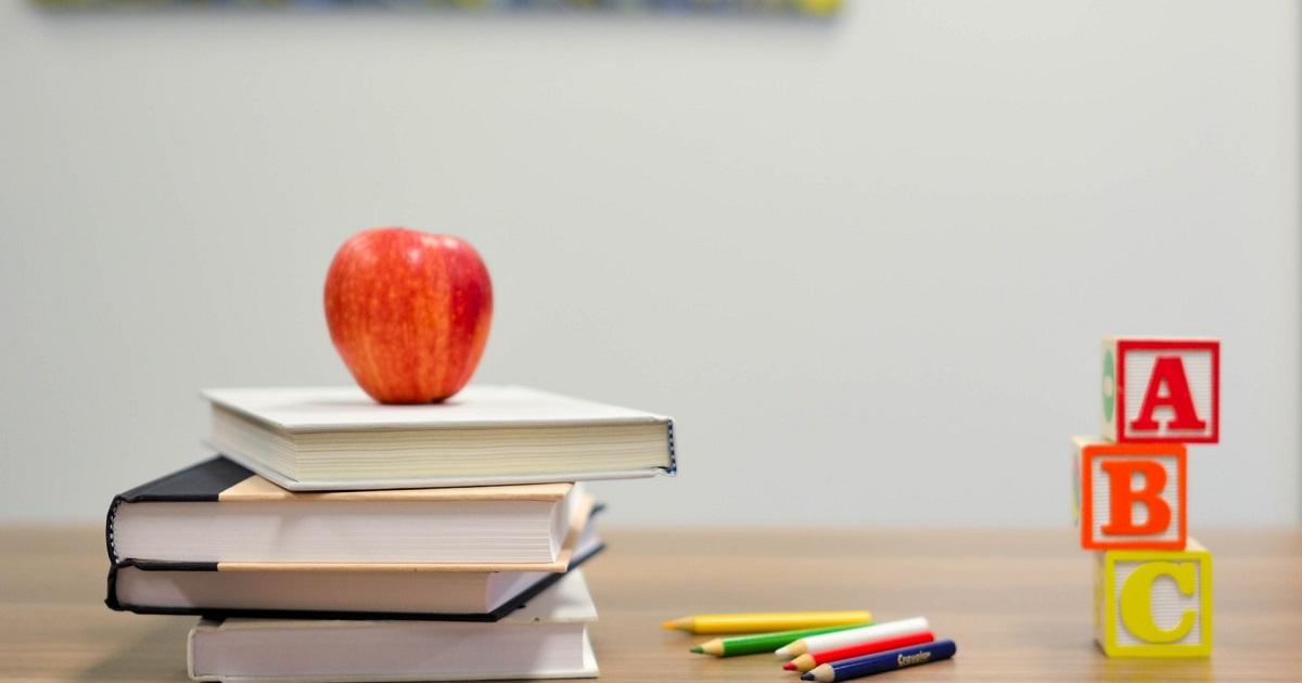 Classroom, desk, book stacks, apple, and alphabet blocks