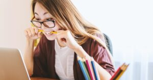 Female online student chewing her pencil looking at laptop