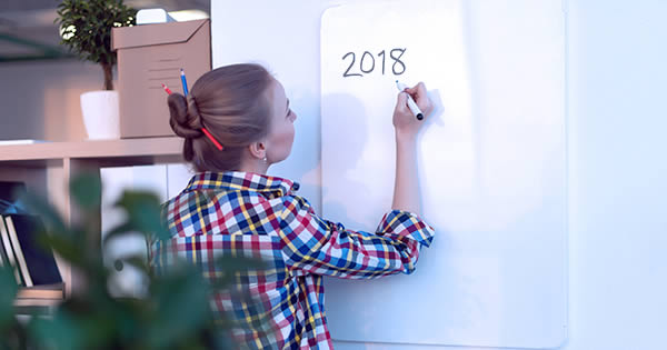 Woman writing 2018 on a dry erase board