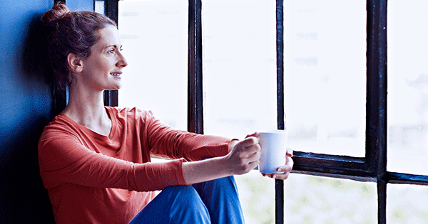 Woman relaxing with a cup of coffee, staring out the window, being mindful.