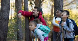 Teacher and kids in the woods.