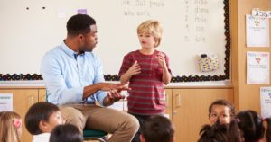 Teacher talking to kid standing in front of class