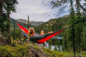 Woman laying in hammock, staring at nature