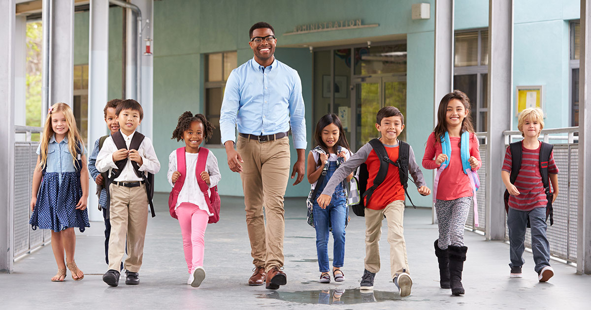 A teacher walking with happy students