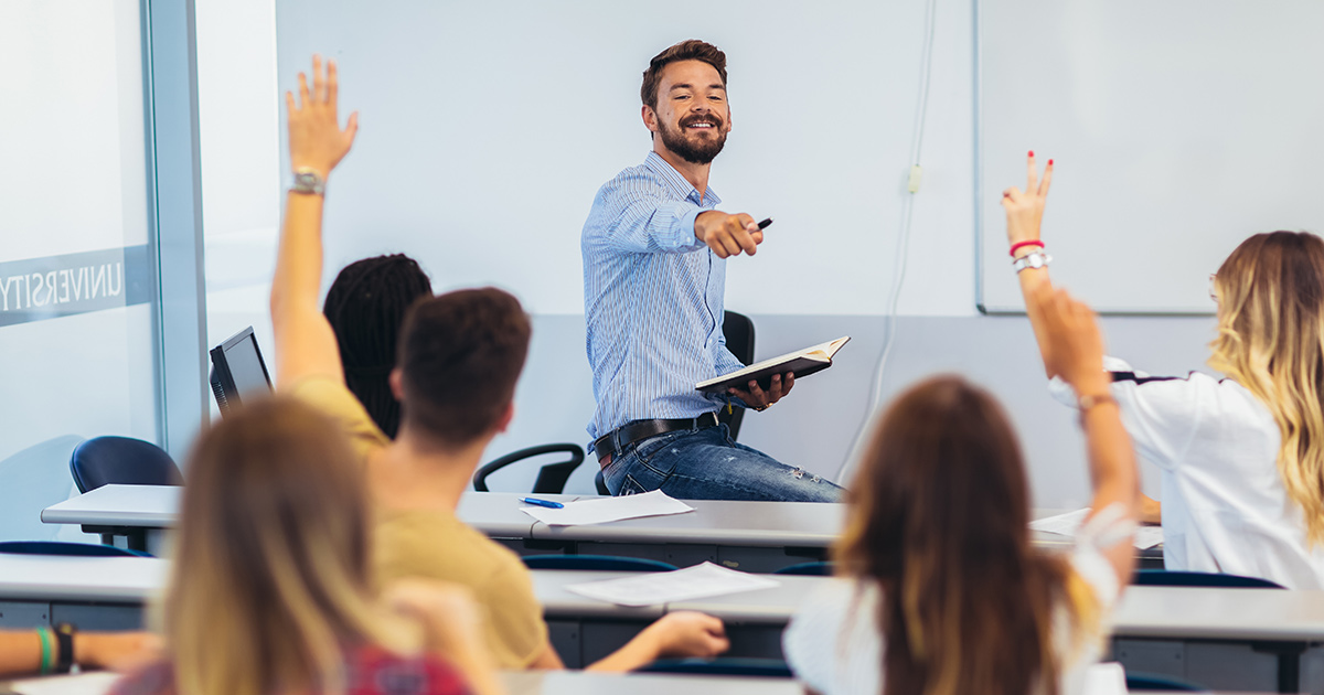 Teacher at whiteboard while students raise hands in classroom
