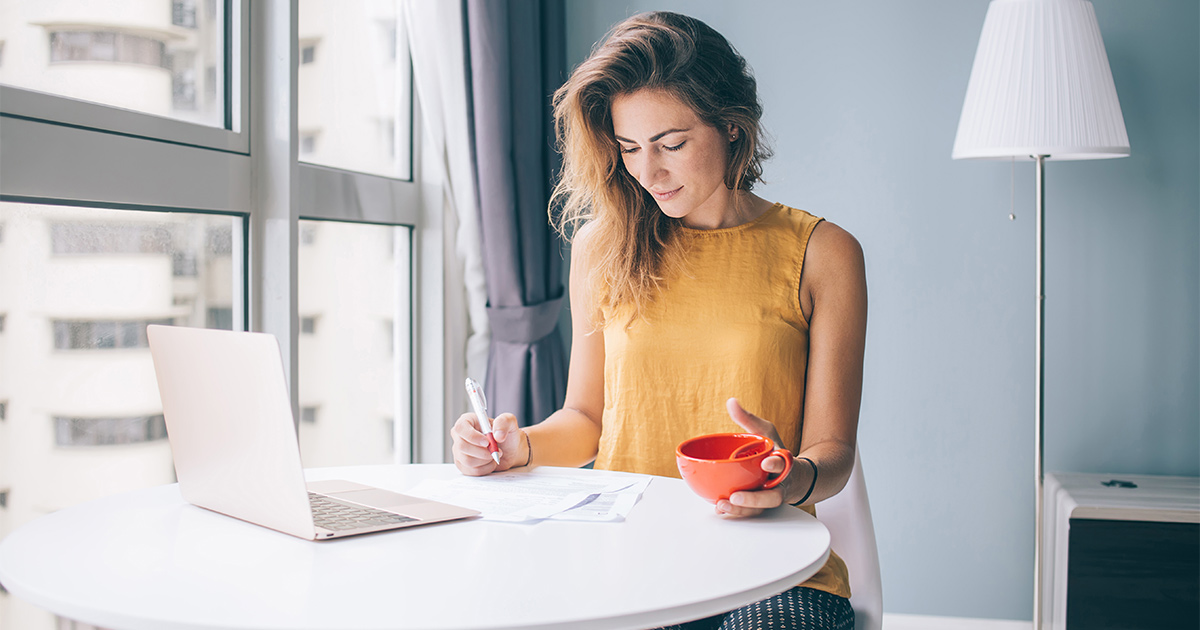 Woman drinking tea at desk with her laptop