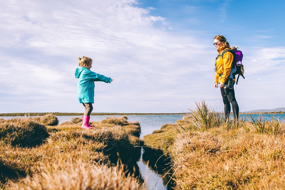 Mother and daughter crossing waterway outdoors
