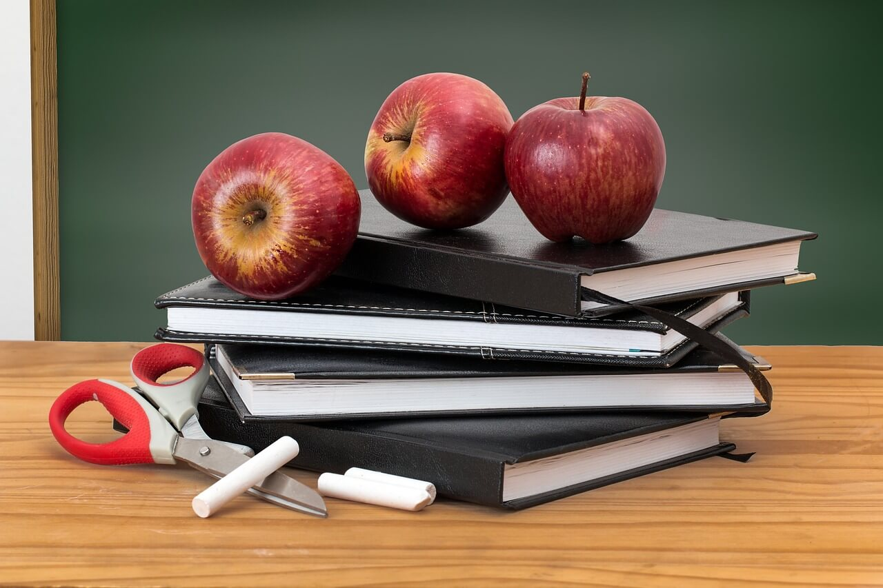 Books, apples, scissors, and school desk