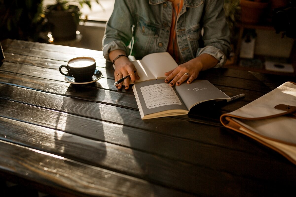 Lady sitting at a wooden table, drinking coffee, and writing in a journal
