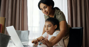 Mother helping her daughter using a laptop