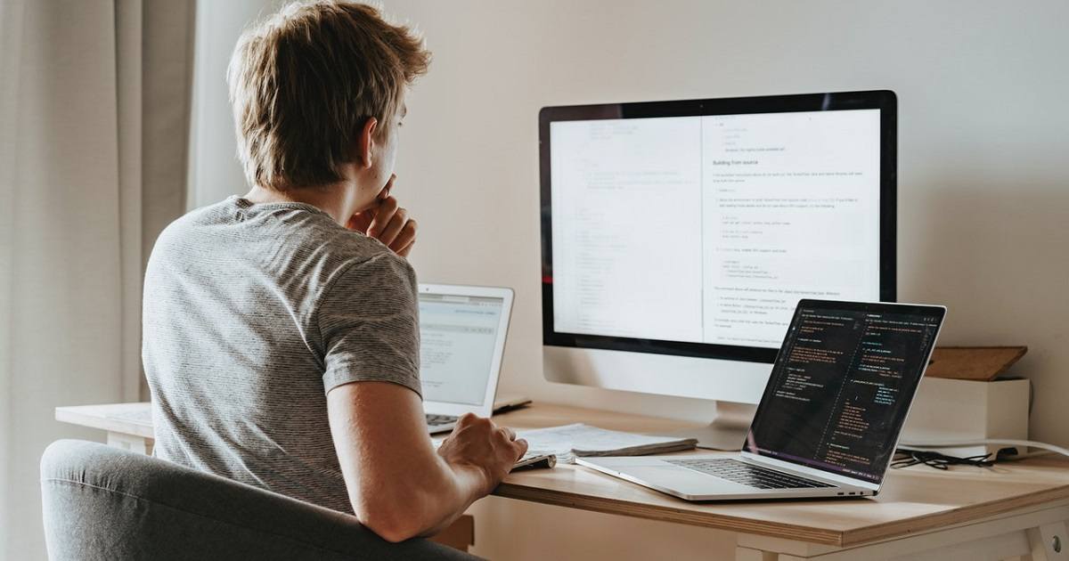 Guy sitting in front of laptop and desktop and monitor, working online