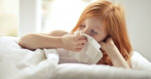 Kid sneezing into tissue
