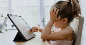 Kid stares and touches at tablet in frustration