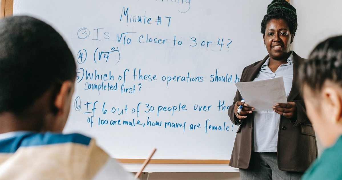 Math teacher standing in front of whiteboard in classroom; two students in foreground